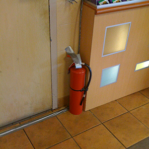 This fire extinguisher is in violation by sitting on the ground.